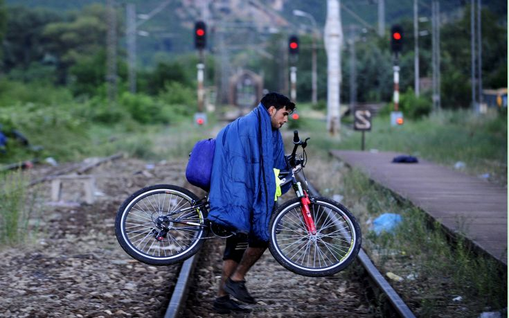 A migrant from Syria carries his bicycle on railway near the Greek border in Macedonia  June 17, 2015.  Hungary announced plans on Wednesday to build a four-metre-high fence along its border with Serbia to stem the flow of illegal migrants. Several thousand migrants are daily crossing the Balkans towards Hungary on their way to other European Union countries. REUTERS/Ognen Teofilovski