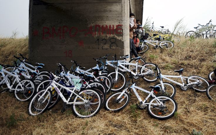 Immigrants from Syria stand near their bicycles as they hide from the rain under a bridge near the Greek border with Macedonia,  June 17, 2015. Hungary announced plans on Wednesday to build a four-metre-high fence along its border with Serbia to stem the flow of illegal migrants. Several thousand migrants are daily crossing the Balkans towards Hungary on their way to other European Union countries.  REUTERS/Ognen Teofilovski       TPX IMAGES OF THE DAY