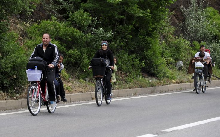Migrants from Syria ride their bicycles near the Greek border in Macedonia June 17, 2015.  Hungary announced plans on Wednesday to build a four-metre-high fence along its border with Serbia to stem the flow of illegal migrants. Tens of thousands of migrants enter Europe through the Balkans from the Middle East and Africa. REUTERS/Ognen Teofilovski