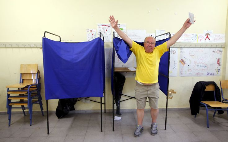 Man raises his arms as he leaves a polling booth before casting his ballot during a referendum vote in Athens, Greece