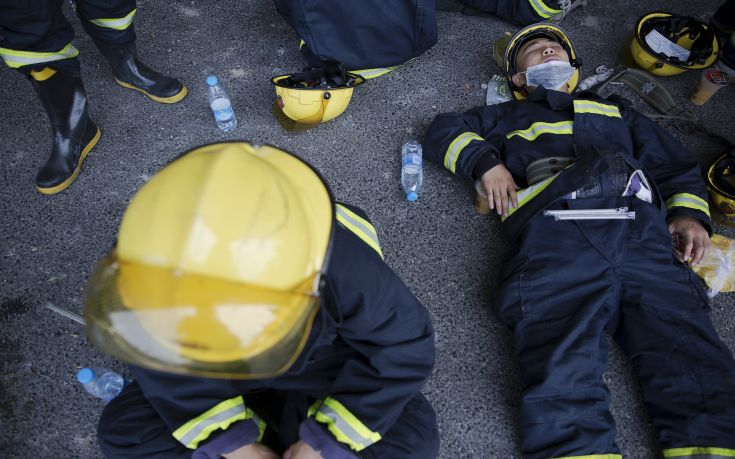 Firefighters take a break after trying to put fire down at the explosion site in Binhai new district in Tianjin, China August 13, 2015. The death toll from two huge explosions that tore through an industrial area in the northeastern Chinese port of Tianjin more than doubled to 44, the official Xinhua news agency said on Thursday.  REUTERS/Damir Sagolj      TPX IMAGES OF THE DAY