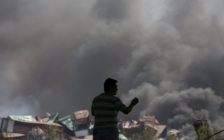 A man looks at smoke pluming from the explosion site in Binhai new district in Tianjin, China August 13, 2015. Two huge explosions tore through an industrial area where toxic chemicals and gas were stored in the northeast Chinese port city of Tianjin, killing at least 44 people, including at least a dozen fire fighters, officials and state media said on Thursday. REUTERS/Damir Sagolj