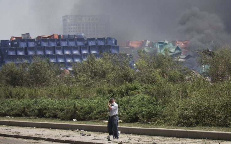 A man adjusts his mask as smoke plumes from the explosion site in Binhai new district in Tianjin, China August 13, 2015. Two huge explosions tore through an industrial area where toxic chemicals and gas were stored in the northeast Chinese port city of Tianjin, killing at least 44 people, including at least a dozen fire fighters, officials and state media said on Thursday. REUTERS/Damir Sagolj