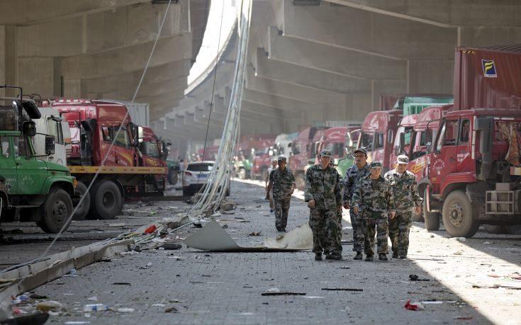 Security personnel walk between damaged trucks near the explosion site takes pictures of pluming smoke in Binhai new district in Tianjin, China August 13, 2015. Two huge explosions tore through an industrial area where toxic chemicals and gas were stored in the northeast Chinese port city of Tianjin, killing at least 44 people, including at least a dozen fire fighters, officials and state media said on Thursday. REUTERS/Damir Sagolj