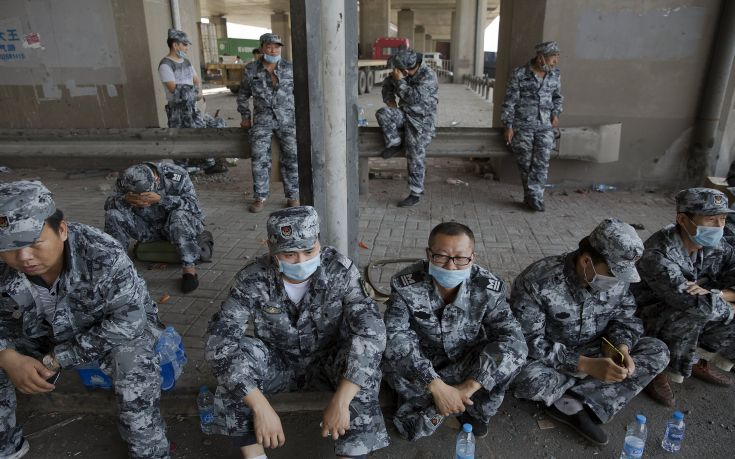 Soldiers rest under the bridge near the explosion site takes pictures of pluming smoke in Binhai new district in Tianjin, China August 13, 2015.Two huge explosions tore through an industrial area where toxic chemicals and gas were stored in the northeast Chinese port city of Tianjin, killing at least 44 people, including at least a dozen fire fighters, officials and state media said on Thursday. REUTERS/Damir Sagolj