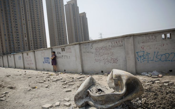 A woman evacuated from a residential area looks at a large metal object that landed and damaged the road about two kilometres from the explosion site in Binhai new district in Tianjin, China August 13, 2015. Two huge explosions tore through an industrial area where toxic chemicals and gas were stored in the northeast Chinese port city of Tianjin, killing at least 44 people, including at least a dozen fire fighters, officials and state media said on Thursday. REUTERS/Damir Sagolj