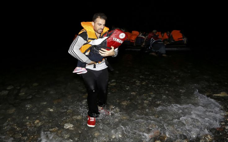 "A Syrian refugee carries a child as they arrive at a beach on the Greek island of Kos after crossing a part of the Aegean sea from Turkey to Greece on a dinghy August 13, 2015. The United Nations refugee agency (UNHCR) called on Greece to take control of the ""total chaos"" on Mediterranean islands, where thousands of migrants have landed. About 124,000 have arrived this year by sea, many via Turkey, according to Vincent Cochetel, UNHCR director for Europe. REUTERS/Yannis Behrakis"