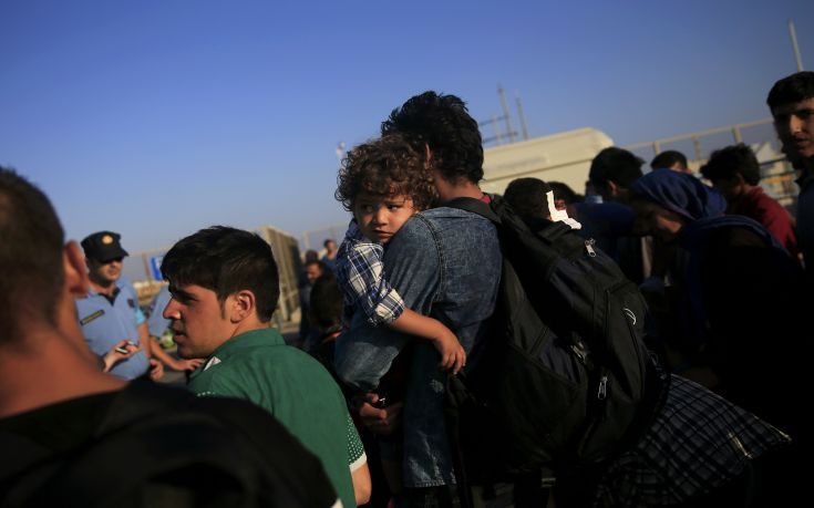 A Syrian child is carried by its father at the port of Kos following a rescue operation off the Greek island of Kos