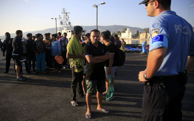 A migrant waits in line next to a Frontex officer at the port of Kos, following a rescue operation off the Greek island of Kos