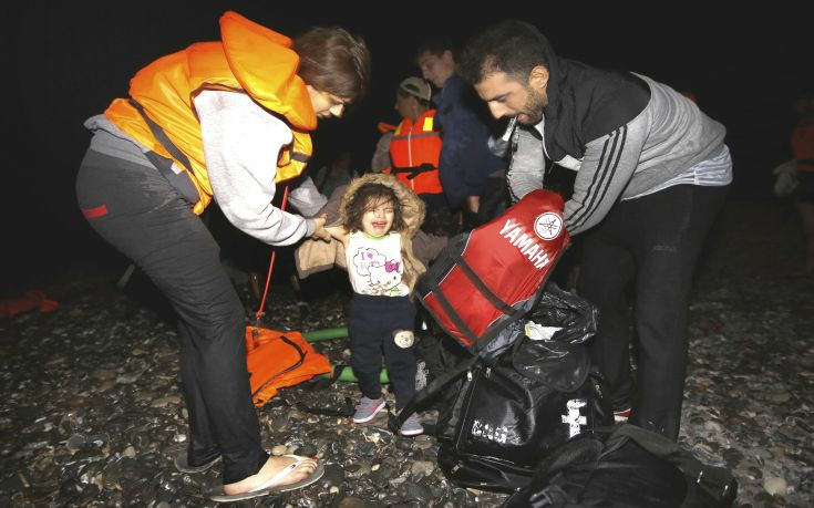 "Syrian refugees dress-up their child with dry clothes moments after arriving at a beach on the Greek island of Kos after crossing a part of the Aegean sea from Turkey to Greece on a dinghy August 13, 2015. The United Nations refugee agency (UNHCR) called on Greece to take control of the ""total chaos"" on Mediterranean islands, where thousands of migrants have landed. About 124,000 have arrived this year by sea, many via Turkey, according to Vincent Cochetel, UNHCR director for Europe. REUTERS/Yannis Behrakis"