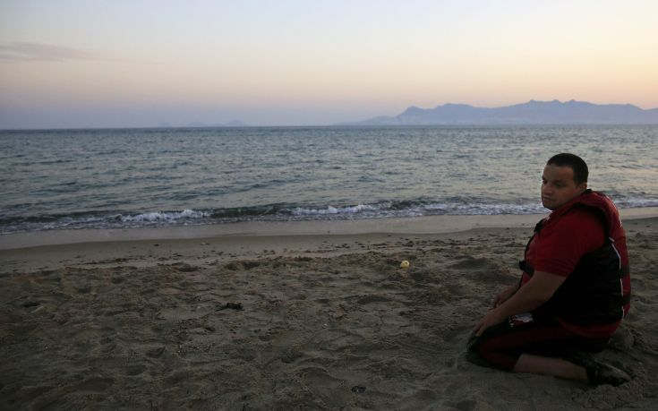 A Syrian refugee prays after landing a beach of the Greek island of Kos