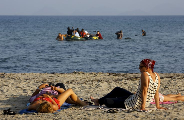 Tourists lie on a beach as migrants and refugees from Syria and Africa arrive on a dinghy at the Greek island of Kos after crossing a part of the Aegean Sea between Turkey and Greece, August 8, 2015. The U.N refugee agency, UNHCR, estimates that Greece has received more than 107,000 refugees and migrants this year, more than double its 43,500 intake of 2014. REUTERS/ Yannis Behrakis