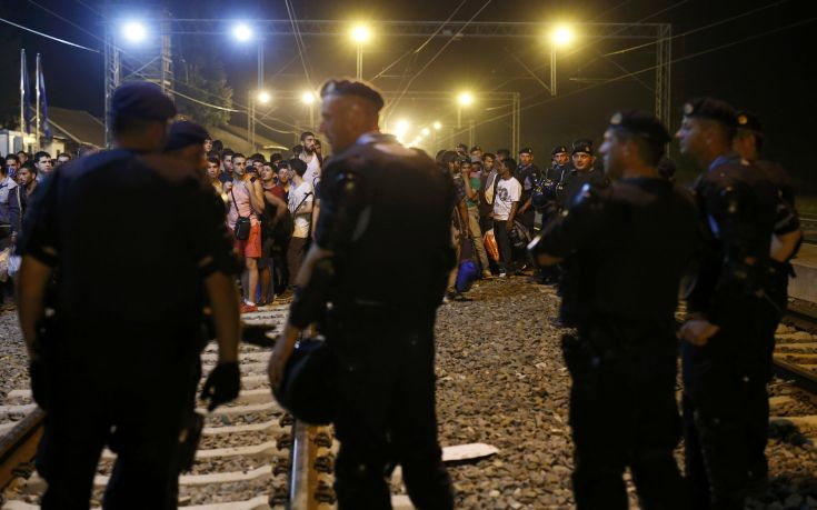 Croatian police stand guard in front of migrants at the train station in Tovarnik