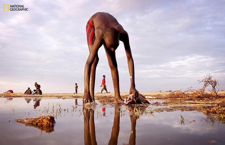 Νεαρός ψαράς καθαρίζει το ψάρι του στη λίμνη Turkana κοντά στα σύνορα της Αιθιοπίας και της Κένυας. Το αγόρι ανήκει στη φυλή Daasanach, τη δεύτερη μικρότερη φυλή της Κένυας με περίπου 60.000- 80.000 μέλη. Φωτογραφία:  Christena Dowsett