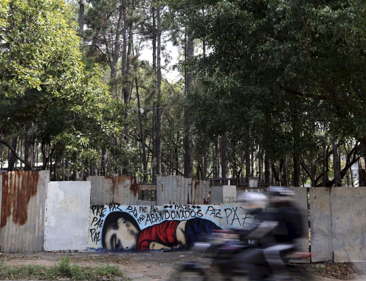 """People on a motorcycle ride past a graffiti depicting the drowned Syrian toddler Aylan Kurdi in Sorocaba, Brazil, September 5, 2015. Brazil's President Dilma Rousseff criticized European nations on Friday for creating """"barriers"""" to the entry of migrants, saying the Syrian child found on a beach in Turkey had died because he was """"not welcome."""" Three-year-old Aylan Kurdi died along with his mother and 5-year-old brother as they attempted to cross the Mediterranean to Greece. Photographs of Kurdi, washed up dead on the shores of Turkey, shocked the world and led to a wave of criticism against the way Europe is dealing with the thousands of refugees fleeing conflict in the Middle East. The graffiti reads: """"Peace, peace, peace, abandoned"""". Picture taken September 5, 2015.  REUTERS/Paulo Whitaker"""