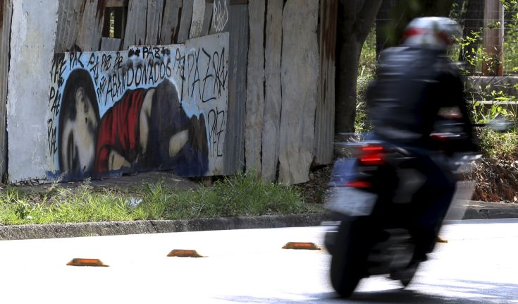 """A motorcycle rides past a graffiti depicting the drowned Syrian toddler Aylan Kurdi in Sorocaba, Brazil, September 5, 2015. Brazil's President Dilma Rousseff criticized European nations on Friday for creating """"barriers"""" to the entry of migrants, saying the Syrian child found on a beach in Turkey had died because he was """"not welcome."""" Three-year-old Aylan Kurdi died along with his mother and 5-year-old brother as they attempted to cross the Mediterranean to Greece. Photographs of Kurdi, washed up dead on the shores of Turkey, shocked the world and led to a wave of criticism against the way Europe is dealing with the thousands of refugees fleeing conflict in the Middle East. The graffiti reads: """"Peace, peace, peace, abandoned"""". Picture taken September 5, 2015.  REUTERS/Paulo Whitaker"""