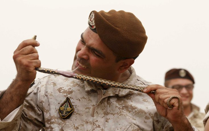 A member of the Lebanese Army's airborne regiment eats snakes during a live drill, held as part of a weapons exhibition during the Security Middle East Show in Beirut