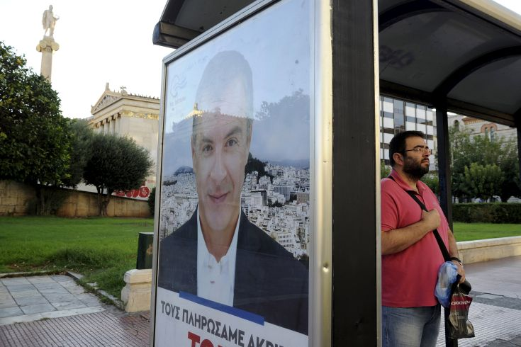 A man stands at a bus stop decorated with a pre-election poster with an image of leader of the centre-left To Potami party Stavros Theodorakis in Athens, Greece, September 17, 2015. Greece's leftist Syriza party has a 0.6 percentage point lead over the conservative New Democracy party, a Kapa Research poll for To Vima newspaper showed on Thursday. REUTERS/Michalis Karagiannis