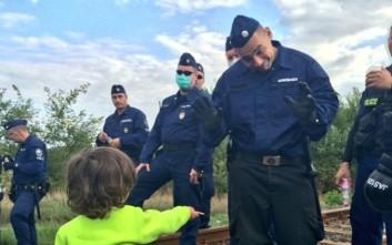 Μικρός πρόσφυγας προσφέρει μπισκότο σε αστυνομικό