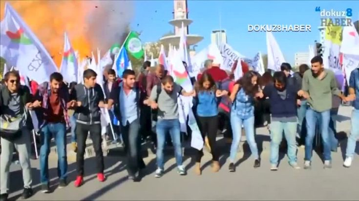 Protesters dance during a peace rally as a blast goes off in Ankara, Turkey October 10, 2015, in this still image taken from a video posted on a social media website. At least 30 people were killed when twin explosions hit a rally of pro-Kurdish and leftist activists outside Ankara's main train station on Saturday in what Turkish President Tayyip Erdogan called a terrorist attack, weeks ahead of an election. REUTERS/Melike Tombalak/dokuz8HABER via Reuters TVATTENTION EDITORS - THIS PICTURE WAS PROVIDED BY A THIRD PARTY. REUTERS IS UNABLE TO INDEPENDENTLY VERIFY THE AUTHENTICITY, CONTENT, LOCATION OR DATE OF THIS IMAGE. FOR EDITORIAL USE ONLY. NOT FOR SALE FOR MARKETING OR ADVERTISING CAMPAIGNS. NO SALES. THIS PICTURE IS DISTRIBUTED EXACTLY AS RECEIVED BY REUTERS, AS A SERVICE TO CLIENTS. TURKEY OUT. NO COMMERCIAL OR EDITORIAL SALES IN TURKEY TPX IMAGES OF THE DAY