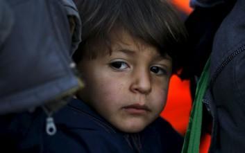 Μαθητές μοιράζουν σακίδια σε μικρά προσφυγόπουλα