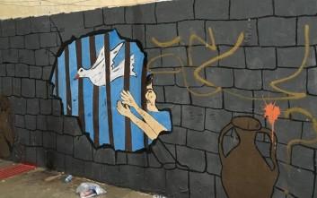 Προσφυγόπουλα γεμίζουν χρώμα τους τοίχους μιας φυλακής