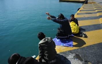 Πρόσφυγας ψαρεύει στο λιμάνι του Πειραιά