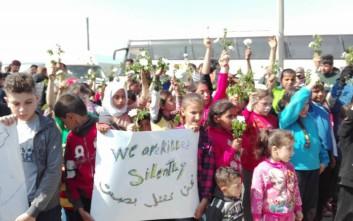 Παιδιά πρόσφυγες με λευκά λουλούδια και πανό στην Ειδομένη