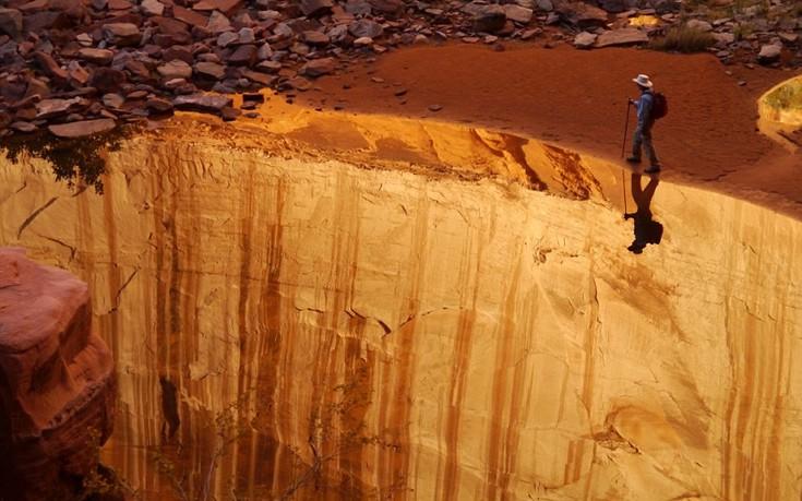 Ο άνδρας της φωτογραφίας μοιάζει να περπατά ένα βήμα από τον γκρεμό αλλά στην πραγματικότητα βαδίζει δίπλα στην εκπληκτική αντανάκλαση του τοπίου στα νερά ποταμού στο Glen Canyon της Γιούτα.