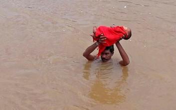 Πατέρας κουβαλάει το άρρωστο μωρό του μέσα στις πλημμύρες για δύο ώρες