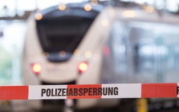 A train stand behind a police cordon in the Central Station in the eastern city of Chemnitz, Germany, Saturday, Oct. 8, 2016. German investigators found several hundred grams of explosives in an apartment they raided Saturday in the eastern city of Chemnitz as they sought a Syrian man suspected of planning a bombing attack. The suspect remained on the run but three contacts were detained and being questioned, police said. (AP Photo/Jens Meyer)