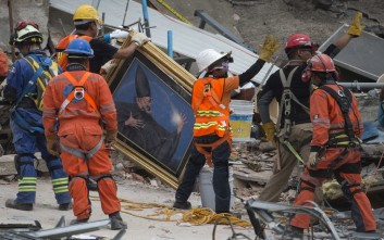 Search and rescue workers remove a painting from a felled office building brought down by a 7.1-magnitude earthquake, as others raise their arms as a sign for people to maintain silence during their search for survivors in the Roma Norte neighborhood of Mexico City, Saturday, Sept. 23, 2017. As rescue operations stretched into day 5, residents throughout the capital have held out hope that dozens still missing might be found alive. (AP Photo/Moises Castillo)