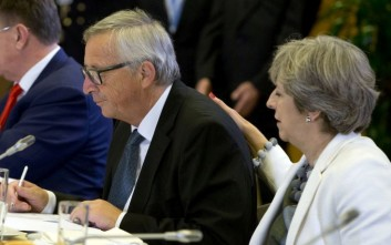 British Prime Minister Theresa May, right, places her hand on the back of European Commission President Jean-Claude Juncker during a breakfast meeting at an EU summit in Brussels on Friday, Oct. 20, 2017. European Union leaders gathered Friday to weigh progress in negotiations on Britain's departure from their club as they look for new ways to speed up the painfully slow moving process. (AP Photo/Virginia Mayo, Pool)
