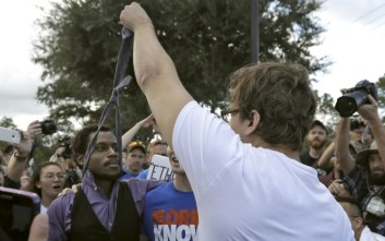 A supporter of white nationalist Richard Spencer grabs ahold of a protester's tie during a clash after a speech by Spencer, Thursday, Oct. 19, 2017, at the University of Florida in Gainesville, Fla. (AP Photo/Chris O'Meara)