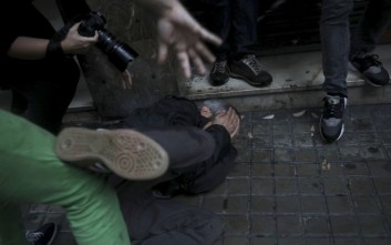 A protester falls on the ground after being hit in the face by a rubber bullet shot by Spanish National Police near the Ramon Llull school assigned to be a polling station by the Catalan government in Barcelona, Spain, early Sunday, 1 Oct. 2017. The Spanish government and its security forces are trying to prevent voting in the independence referendum, which is backed by Catalan regional authorities. Spanish officials had said force wouldn't be used, but that voting wouldn't be allowed. (AP Photo/Manu Brabo)