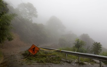 A men at work sign stands on a washed out road in Alajuelita on the outskirts of San Jose, Costa Rica, Thursday, Oct. 5, 2017. Tropical Storm Nate formed off the coast of Nicaragua on Thursday and was being blamed for at least 17 deaths in Central America as it spun north toward a potential landfall on the U.S. Gulf Coast as a hurricane over the weekend. (AP Photo/Moises Castillo)
