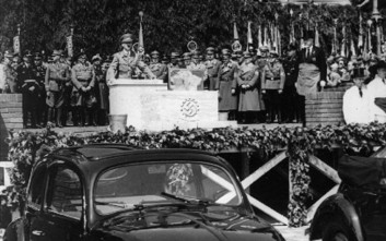 """ARCHIV -  Adolf Hitler spricht am 26. Mai 1938 in Fallersleben bei Hannover vor der Grundsteinlegung einer neuen Automobil-Fabrik hinter einem Kaefer Automobil. Am 17. Januar 1934 verfasste er sein """"Expose betreffend den Bau eines deutschen Volkswagens"""". AP provides access to this publicly distributed HANDOUT photo to be used only to illustrate news reporting or commentary on the facts or events depicted in this image.  (AP Photo) ** APD4163 ** --- FILE -  Adolf Hitler speaks on the podium prior to laying the cornerstone for a giant automobile factory in Fallersleben near Hanover, Germany, May 26, 1938. In front stands a beetle car. (AP Photo)"""