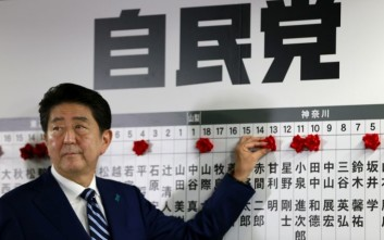 Japanese Prime Minister Shinzo Abe, leader of the Liberal Democratic Party, poses for photos as he marks on the name of one of those elected in the parliamentary lower house election at the party headquarters in Tokyo, Sunday, Oct. 22, 2017.  Japanese media projected shortly after polls closed that Prime Minister Shinzo Abe's ruling coalition would win a clear majority in national elections. (AP Photo/Shizuo Kambayashi)
