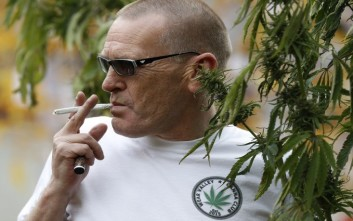 Fraser Lightbody from Teesside Cannabis Club poses with a Hemp plant during a cannabis rally near Parliament in London, Tuesday, Oct. 10, 2017. The rally was to help raise awareness of the medical use of cannabis.(AP Photo/Kirsty Wigglesworth)