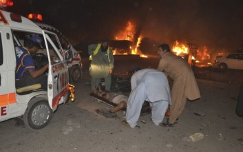"""Pakistani volunteers help an injured person awaiting an ambulance to take them to a hospital in Quetta, Pakistan, Saturday, Aug. 12, 2017. Pakistan's army says """"terrorists"""" have targeted a military truck with a bomb killing many soldiers and civilians and several injured. (AP Photo/Arshad Butt)"""