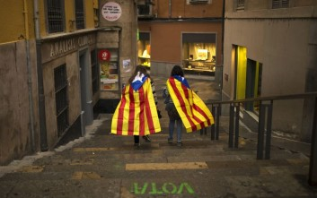"Women with ""esteladas,"" or Catalonia independence flag, walk along the old quarter in Girona, Spain, Monday, Oct. 2, 2017. Catalonia's government will hold a closed-door Cabinet meeting Monday to discuss the next steps in its plan to declare independence from Spain following a disputed referendum marred by violence. Regional officials say the vote, which Spain insists was illegal and invalid, shows that a majority favor secession. (AP Photo/Francisco Seco)"
