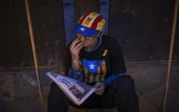 """A man wearing clothes decorated with independence flags reads a newspaper outside the Catalan parliament, in Barcelona, Spain, Thursday, Oct. 26, 2017. Puigdemont said Thursday he considered calling a snap election, but was choosing not to because he didn't receive enough guarantees that the government's """"abusive"""" moves to take control of Catalonia would be suspended. (AP Photo/Emilio Morenatti)"""