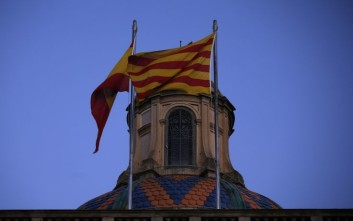 A Catalan and Spanish flag flutter on top of the Palau Generalitat in Barcelona, Spain, early Monday Oct. 30, 2017. Hundreds of thousands of Catalans took to the streets of Barcelona Sunday to call for their region to remain part of Spain, two days after regional lawmakers exacerbated a political crisis by voting for the wealthy region to secede. (AP Photo/Manu Fernandez)