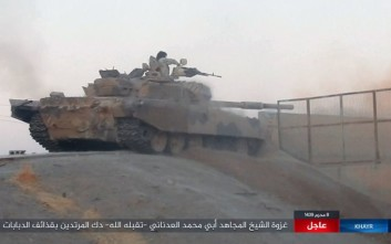"This image posted online on Thursday, Sept. 28, 2017, by supporters of the Islamic State militant group on an anonymous photo sharing website, purports to show a tank operated by the group firing at Syrian troops in the eastern Syrian province of Deir el-Zour. The Arabic caption reads, ""The incursion of Sheikh Abu Mohammed al-Adnani may God give him mercy. Pounding of infidels with tank shells."" (militant photo via AP)"