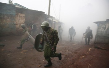 Riot police are caught in tear gas during running battle with opposition supporters in Kibera Slums in Nairobi, Kenya, Thursday, Oct. 26, 2017. Kenya is holding the rerun of its disputed presidential election Thursday, despite a boycott by the main opposition party and rising political tensions in the East African country. (AP Photo/Brian Inganga )