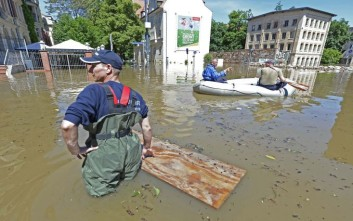 A resident stands in front of a boat in an area flooded by river Saale in Halle, central Germany, Wednesday, June 5, 2013. Heavy rainfalls cause flooding along rivers and lakes in Germany, Austria, Switzerland, the Czech Republic and Hungary. (AP Photo/Jens Meyer)