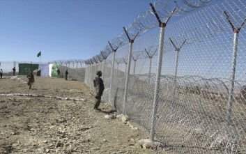 Pakistani soldiers stand guard at newly erected fence between Pakistan and Afghanistan at Angore Adda, Pakistan, Wednesday, Oct. 18, 2017. Pakistan's military says new fencing and guard posts along the border with Afghanistan will help prevent militant attacks, but the stepped-up fortifications have angered Kabul, which does not recognize the frontier as an international border. (AP Photo/Mohammad Yousaf)