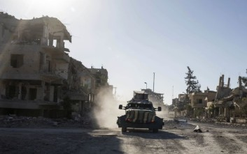 An armored vehicle drives through the city of Raqqa, Syria, Wednesday, Oct. 18, 2017. U.S.-backed Syrian Democratic Forces (SDF) were removing land mines and clearing roads in the northern city a day after commanders said they had driven the Islamic State group from its de facto capital. (AP Photo/Asmaa Waguih)