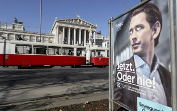 An election poster of the conservative Austrian People's Party, OEVP, stands in front of the parliament in Vienna, Austria, Monday, Oct. 16, 2017. Hundreds of thousands of ballots must still be counted in Austria's general elections, but the tally is not likely to substantially change results that have put 31-year old Foreign Minister Sebastian Kurz on track to become Europe's youngest leader. (AP Photo/Ronald Zak)