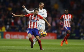 Real Madrid's Cristiano Ronaldo, right, tussles for the ball with Atletico Madrid's Juanfran during the Spanish La Liga soccer match between Real Madrid and Atletico at the Wanda Metropolitano stadium in Madrid, Saturday, Nov 18, 2017. (AP Photo/Francisco Seco)